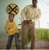 Image of a man and his pre-teen son are dancing and laughing