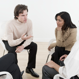 Image of a man and a woman talking to each other in a support group