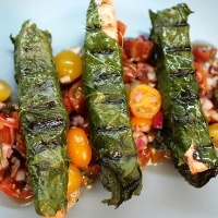 Image of Grilled Fish Wrapped in Grape Leaves with Cherry Tomatoes