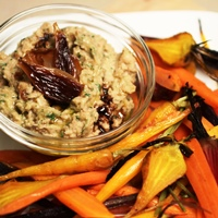 Image of A plate of white bean hummus with caramelized onions surrounded by honey roasted carrots