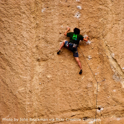 image of a man climbing a rock wall