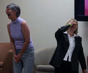 two women laughing so hard that they're near tears during a laughter class