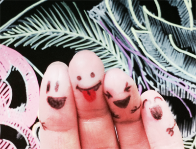 Image of smiley faces drawn on someone's fingers