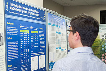 A man looks at a research poster